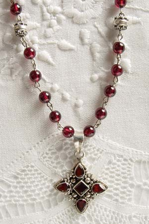 Garnet w 1-1/4 in faceted garnet cross